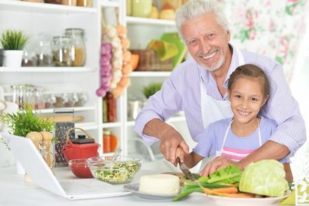 Älterer Mann mit der Enkelin, die Abendessen in der Küche vorbereitet
