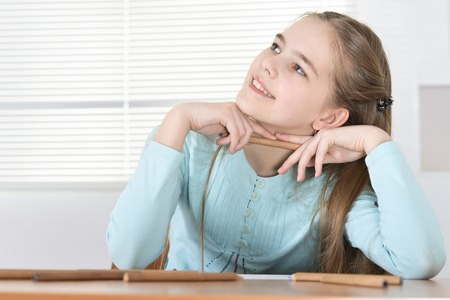Portrait of cute schoolgirl sitting at table and drawing