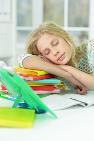 Portrait of tired schoolgirl sleeping at desk after studying at home