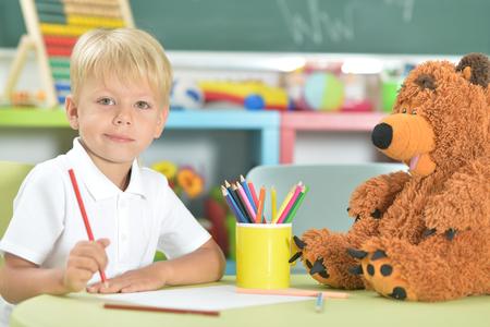 Cute little boy drawing with pencils in classroom Фото со стока - 109389160