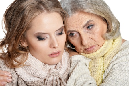 Sad senior woman with daughter posing on white background