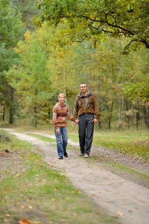 father and son walking on road in autumn forest 스톡 콘텐츠