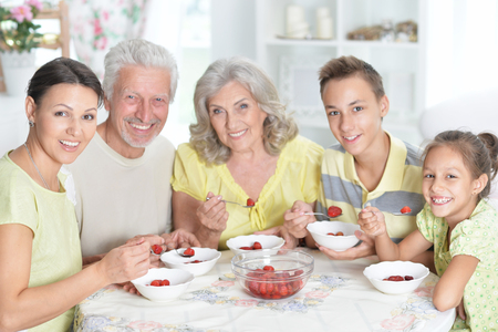 Portrait of big happy family eating fresh strawberries