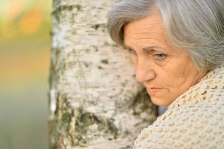 Portrait of senior woman by the tree Imagens - 109713477