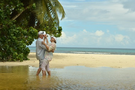 Happy elderly couple dancing at tropical beach