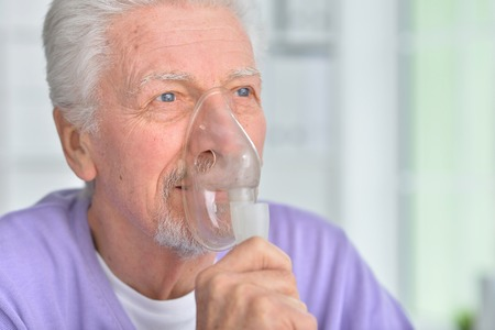 Portrait of senior man with inhaler at home Stock Photo