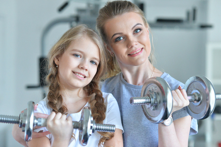 Sporty young woman training with teenage daughter