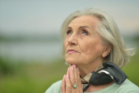 Portrait of smiling elderly woman posing outdoors