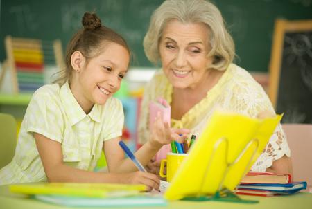 Portrait of grandmother with little girl doing homework Imagens