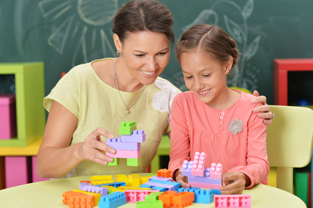 Curly little girl and her mother playing with colorful plastic b Фото со стока - 109885486