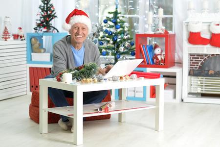 Portrait of happy senior man with laptop
