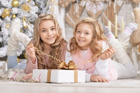 Portrait of cute little girls with gift posing