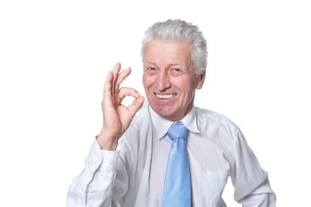 Portrait of senior businessman in formal wear showing o Imagens
