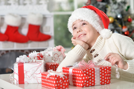 Portrait of cute little boy in Santa hat with gifts for Christmas Stockfoto