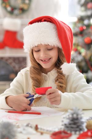 Portrait of cute little girl in Santa hat preparing for Christmas Stockfoto