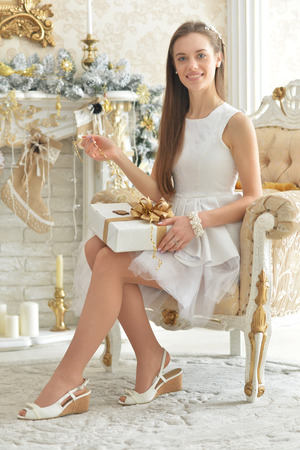 Portrait of a beautiful young woman posing in room decorated for Christmas holiday Stock Photo
