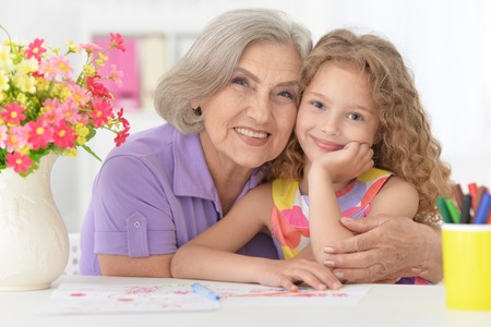 Portrait of schoolgirl studying with grandmother at home Banque d'images