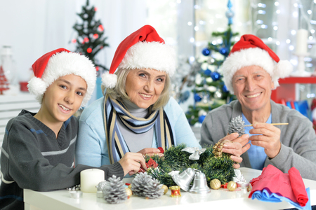 Portraint of grandparents with boy preparing for Christmas