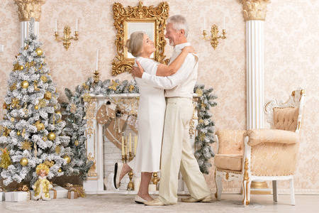 Portrait of a cute happy olderly couple dancing near christmas tree