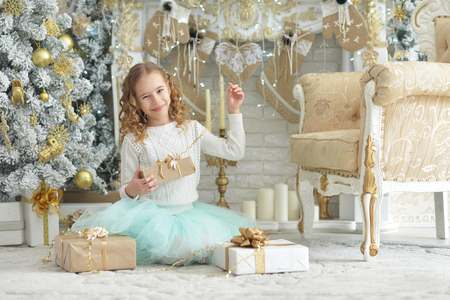 Portrait of cute happy girl sitting with Christmas presents