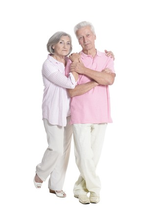 portrait of senior couple embracing on white background