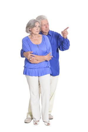 portrait of senior couple pointing something isolated on white background