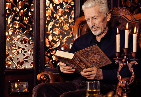 Portrait of senior man reading book while sitting