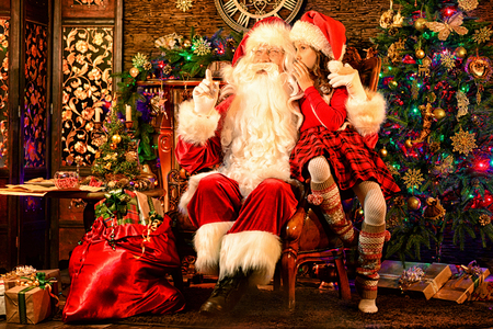Little girl with Santa Claus in room