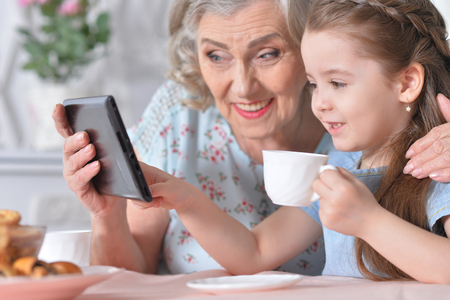Cute little girl with her grandmother looking at tablet