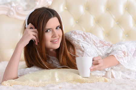 Portrait of young woman lying on bed Stock Photo