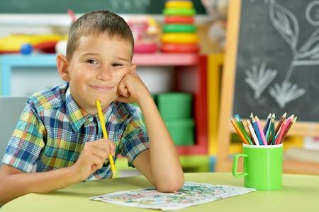 Porträt des kleinen Jungen, der mit Bleistift zeichnet