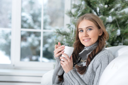 Portrait of cute young woman with cup of tea