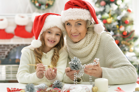 Grandmother and her little granddaughter preparing for Christmas together at home, painting pine cone
