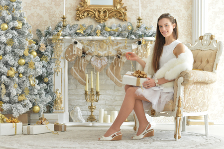Young woman posing in room decorated for Christmas holiday