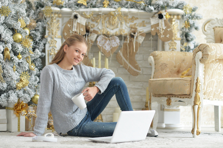 Portrait of teenage girl using laptop while sitting near Christmas tree