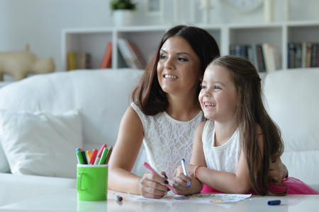 Portrait of cute mother and daughter painting Stock Photo