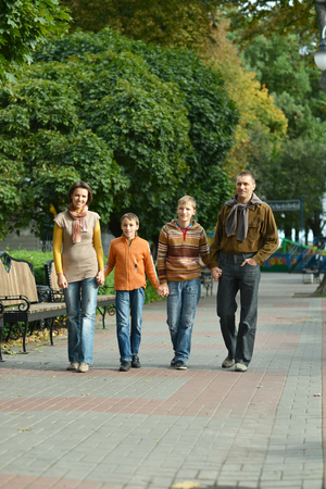 Family of four relaxing  in autumn park Imagens