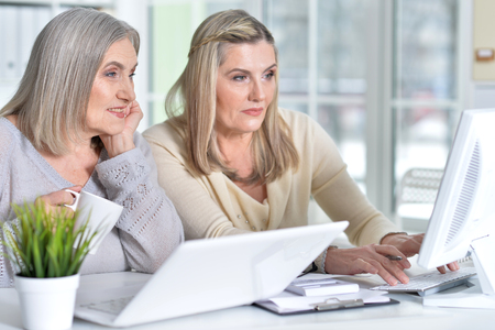 Two excited mature women working in office Фото со стока
