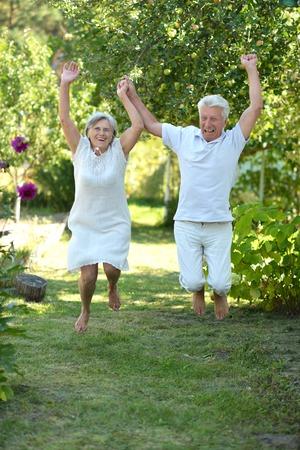 Happy elder couple having fun in the late spring park Stock Photo
