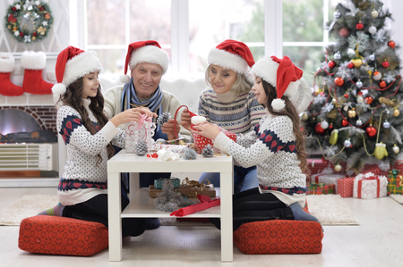 Happy grandparents with twin girls preparing for Christmas at home