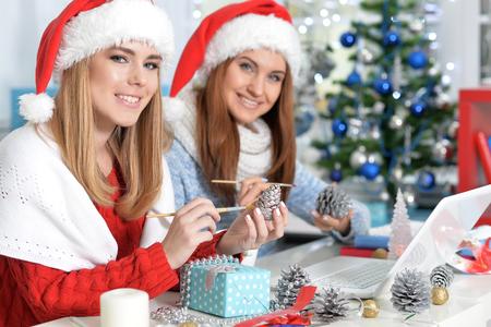Young smiling women in Santa hats using laptop 免版税图像
