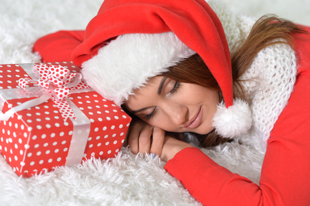 Portrait of cute woman with Christmas gift sleeping