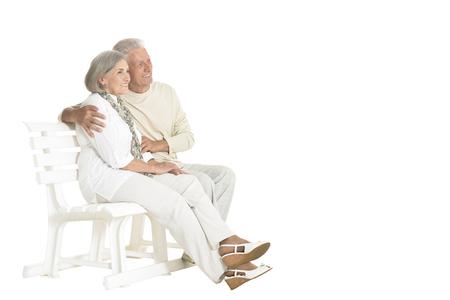 Portrait of senior couple sitting on bench on white background 写真素材