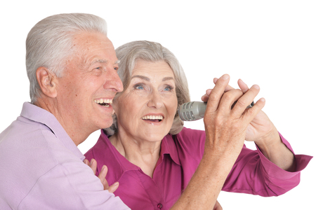 Senior couple singing karaoke on white background