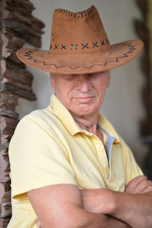 Portrait of nice mature man in cowboy hat