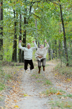 Portrait of senior couple walking in autumn forest