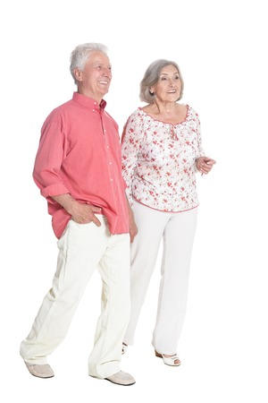 Portrait of senior couple holding hands on white background, full length