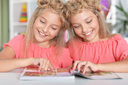 two adorable twin sisters with modern hairstyles Stock Photo