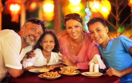 Portrait of a family sitting at table at cafe and having dinner