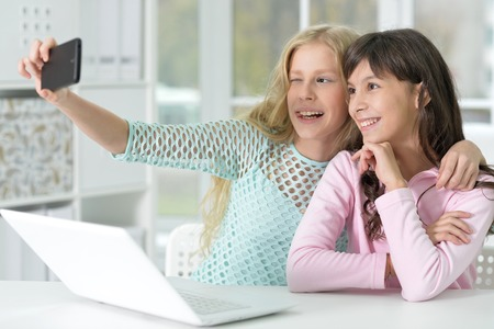 Portrait of two girls with phone and laptop